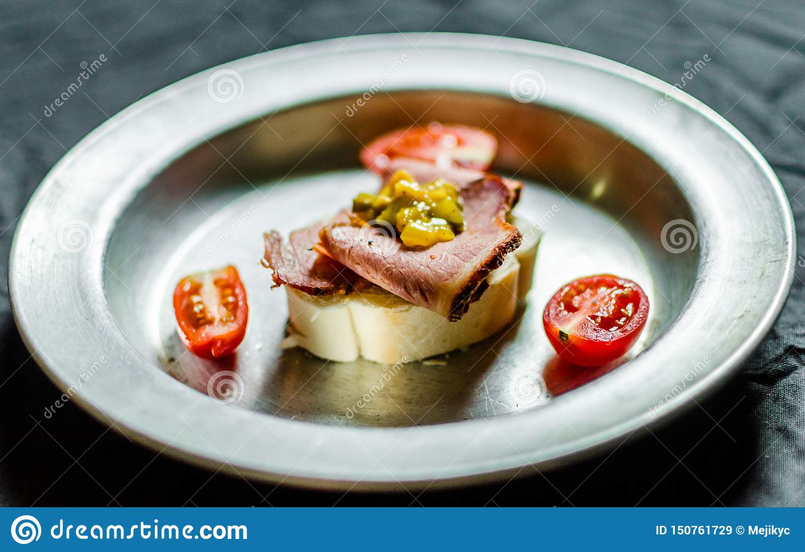 Jewish appetizer sandwich with pastrami, mustard relish, and cherry tomatoes