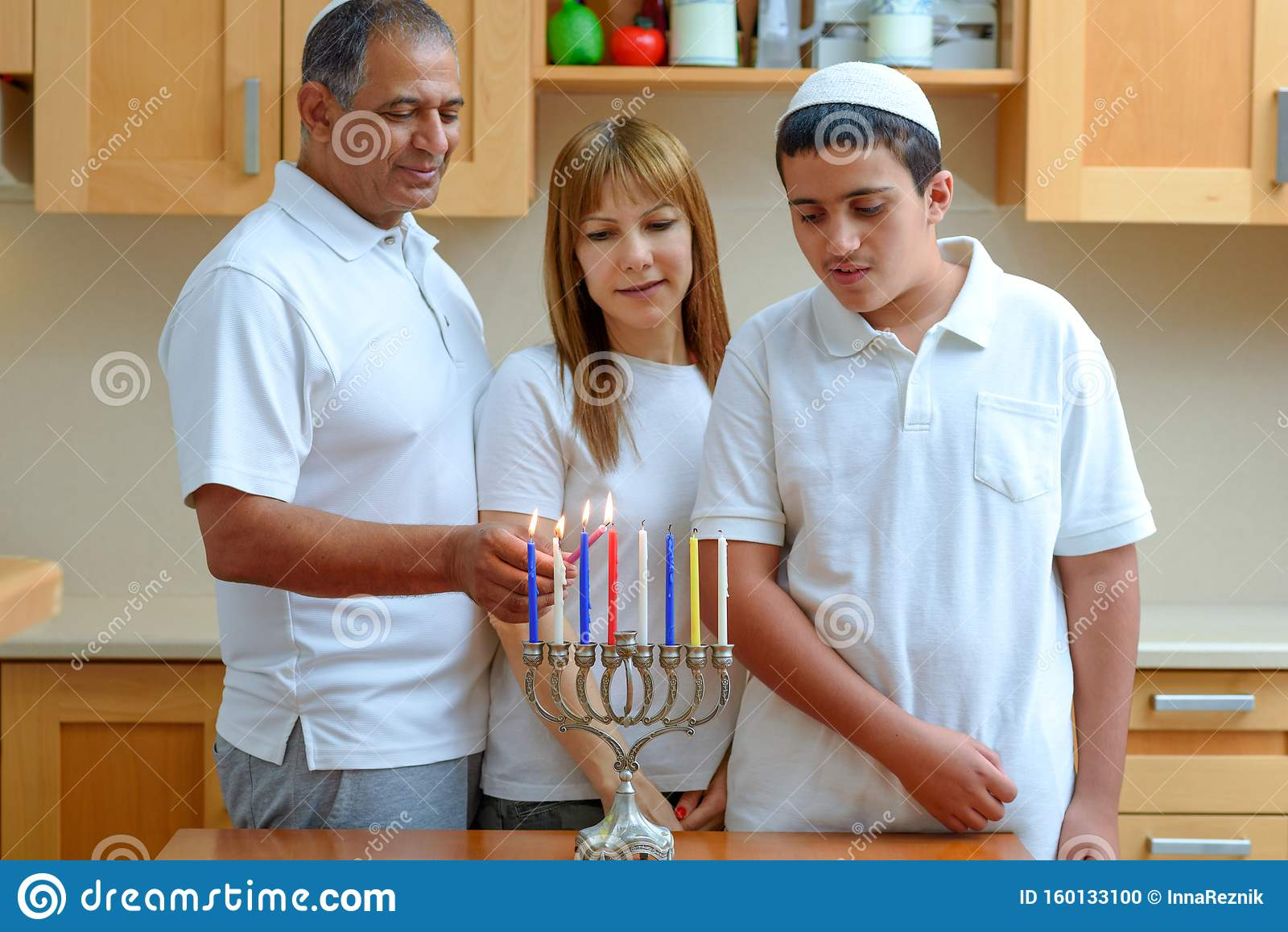 Jewish Dad, Mom and teenager son lighting Chanukkah Candles in a menorah for holidays