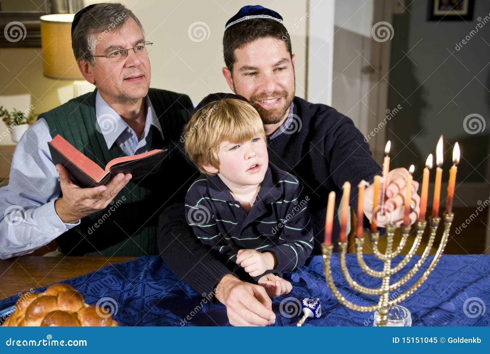Jewish family lighting Hanukkah menorah