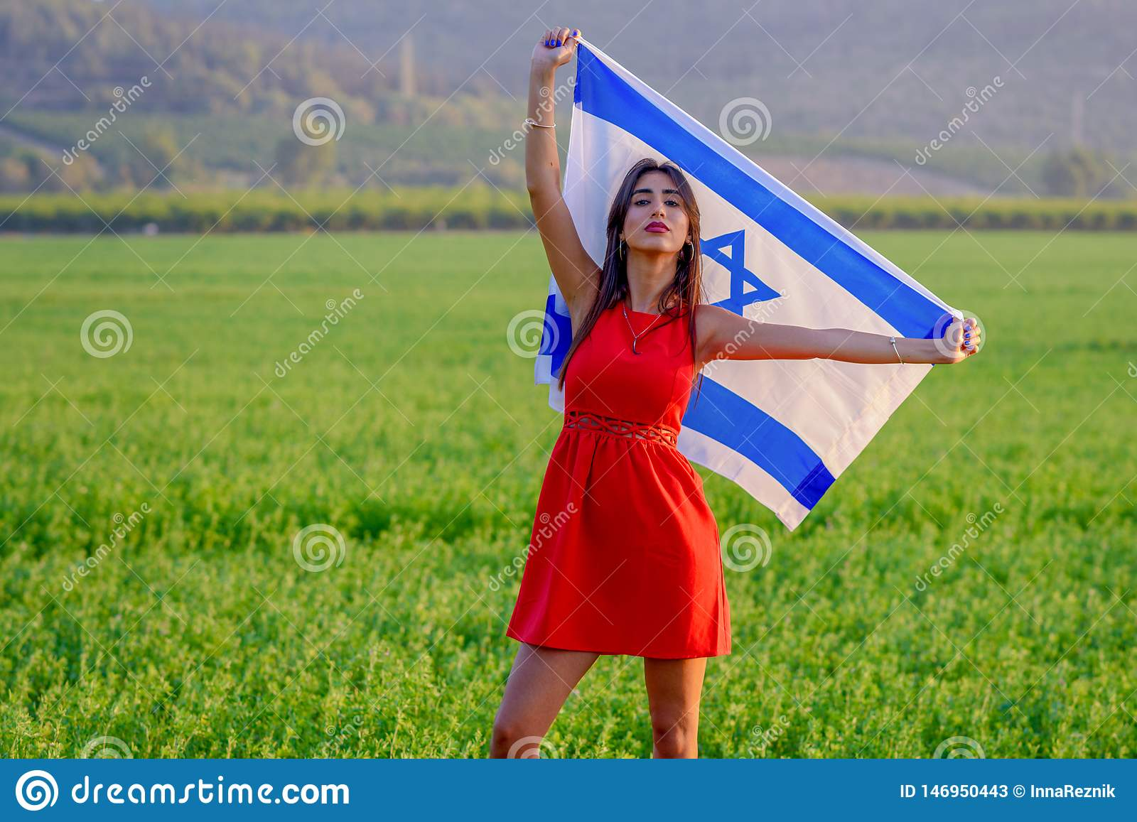 Jewish girl with flag of Israel on amazing landscape in beautiful summer.