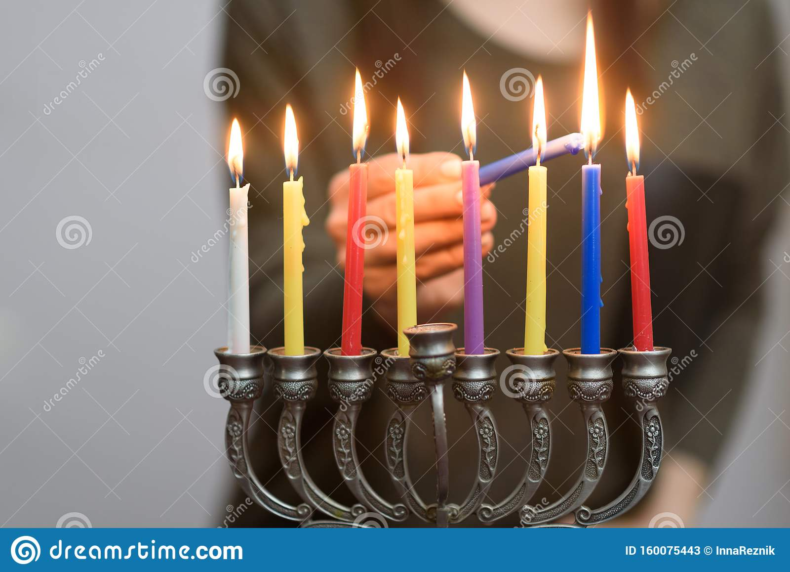 Jewish Woman lighting Hanukkah Candles in a menorah.