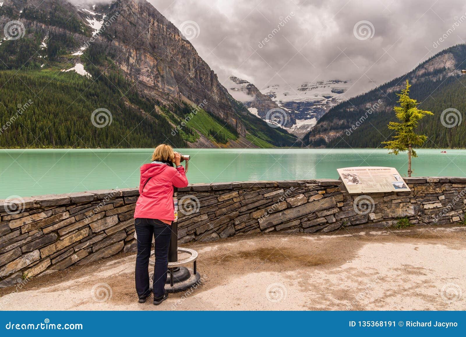 Jeziornego Louise turysty przegląda góry Kanada i chmurny niebo