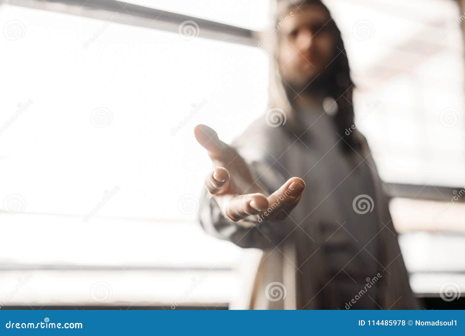 Jezus Chrystus w białym kontuszu dosięga out jego ręka