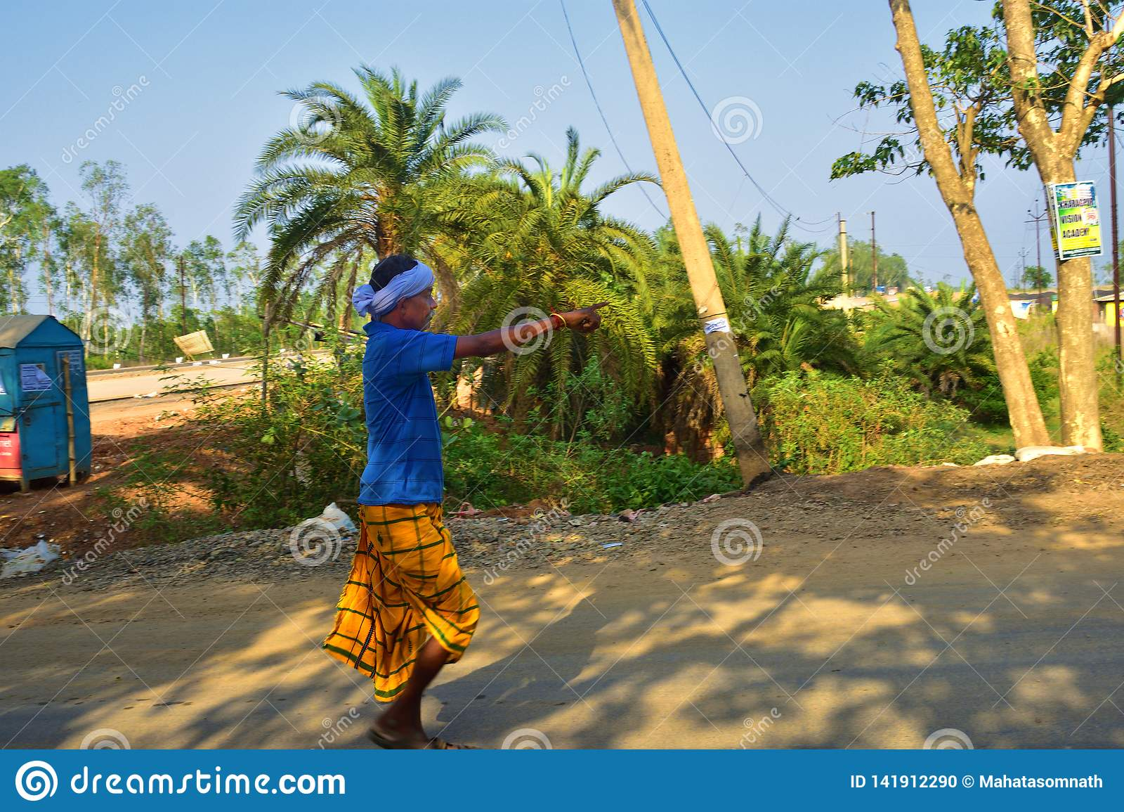 Jhargram, West Bengal, India- April 28, 2018: an old santal an Indian tribe old man was walking and pointing ahead with his