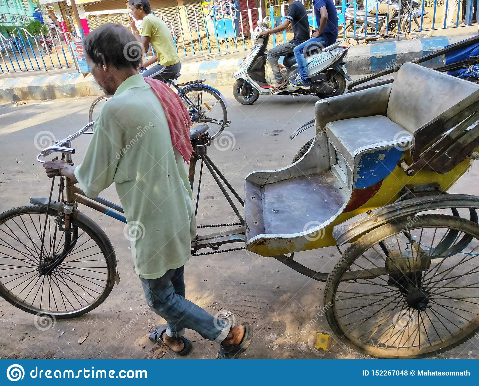 Jhargram, West Bengal, India - May 05, 2019: A hand pulled rickshwa was pulled by someone on a busy road of a city in West Bengal