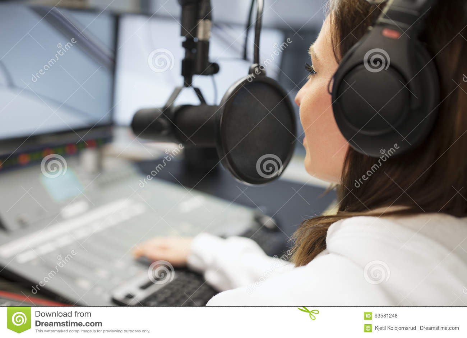 Jinete Wearing Headphones While que usa el micrófono en el estudio de radio