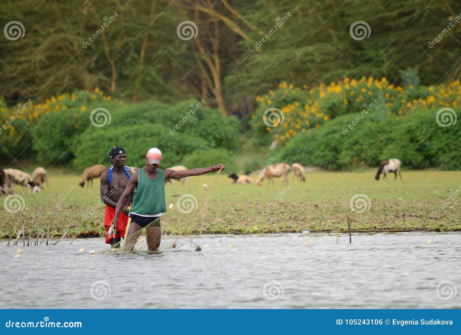 JINJA, UGANDA - OKOŁO OCT, 2017: Życie codzienne w Jinja Młodzi ludzie robią ich życie codzienne pracom przy brzeg rzeki Nil, Jin