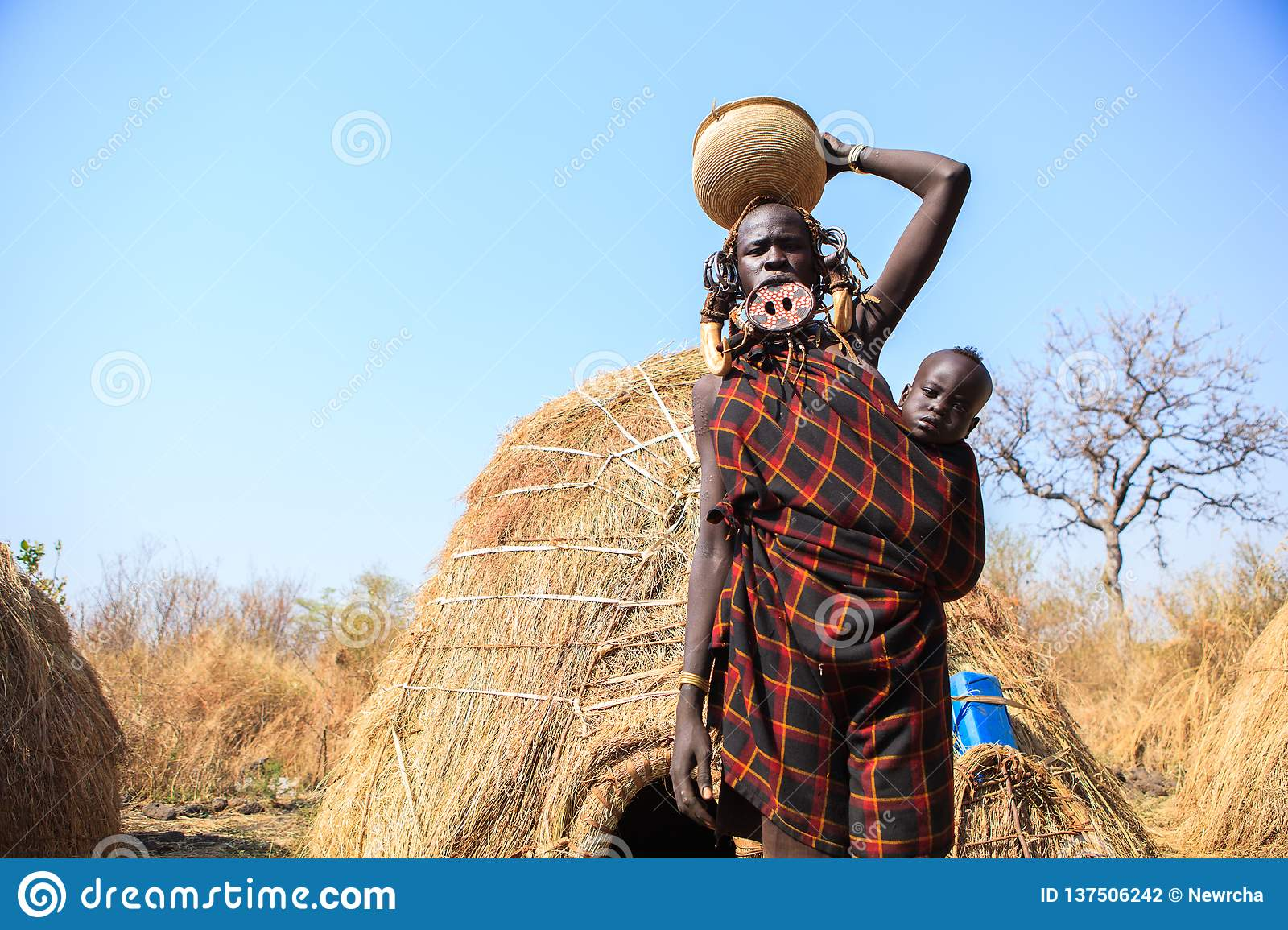Mursi tribe lady carrying her baby