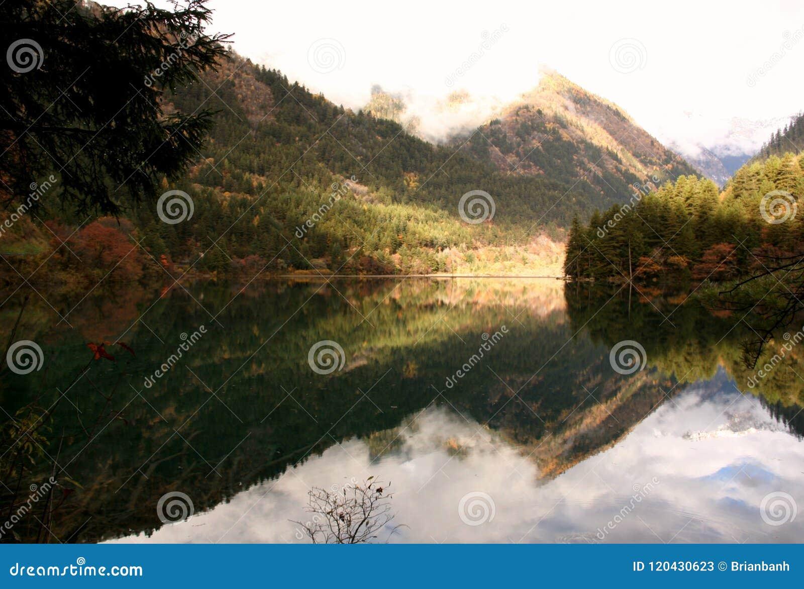 "Jiuzhaigou's ""Mirror Lake"" reflecting the Min mountains on a calm morning in Sichuan, China."