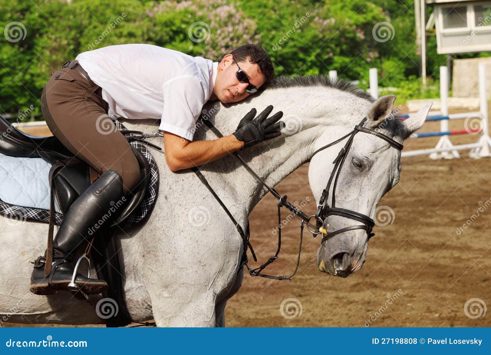 Jockey in den Gläsern umarmen Pferd