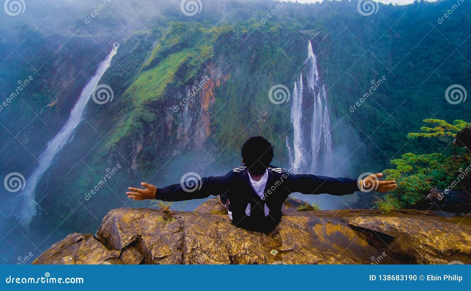 Jog falls . guy enjoying the beautiful nature view