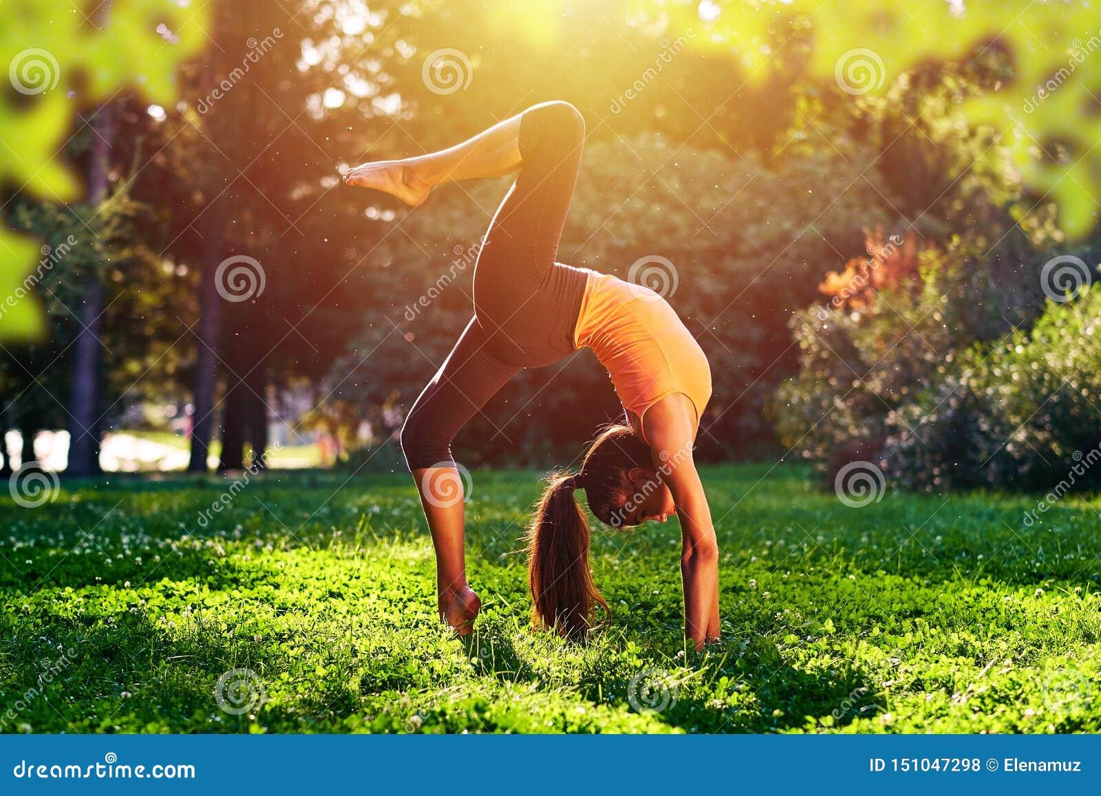 Joga Brid?owy ?wiczenie M?odej kobiety ?wiczy joga, rozci?ganie w naturze przy parkiem lub taniec lub Zdrowie stylu ?ycia poj?cie