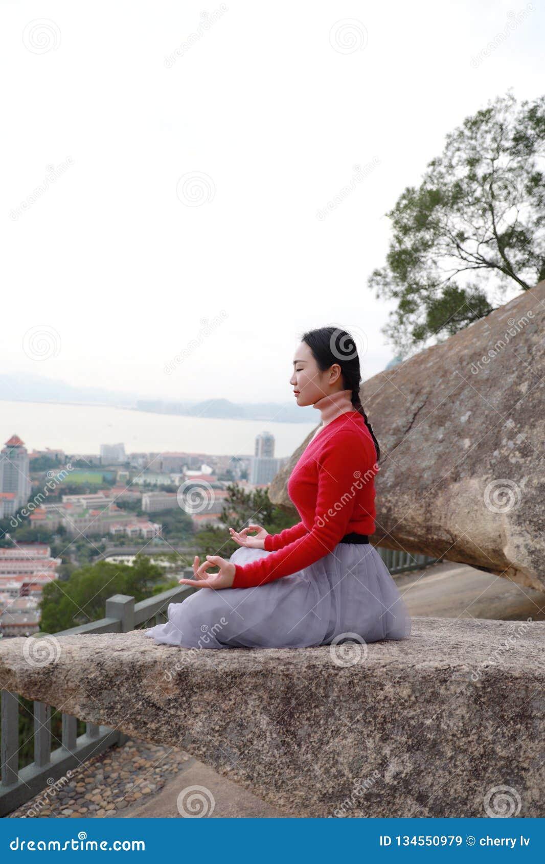 Joga kobieta siedzi w medytacji pozie na halnego szczytu skale