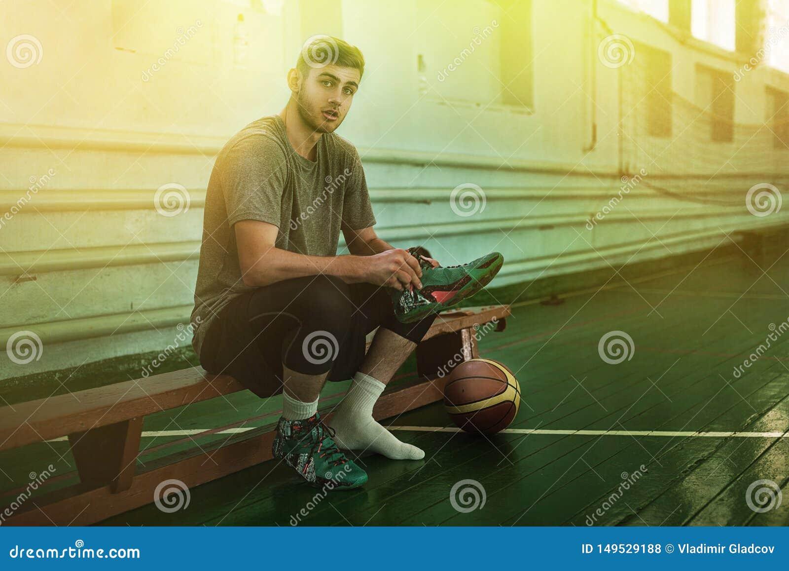 Jogador de basquetebol novo em um campo de b?squete