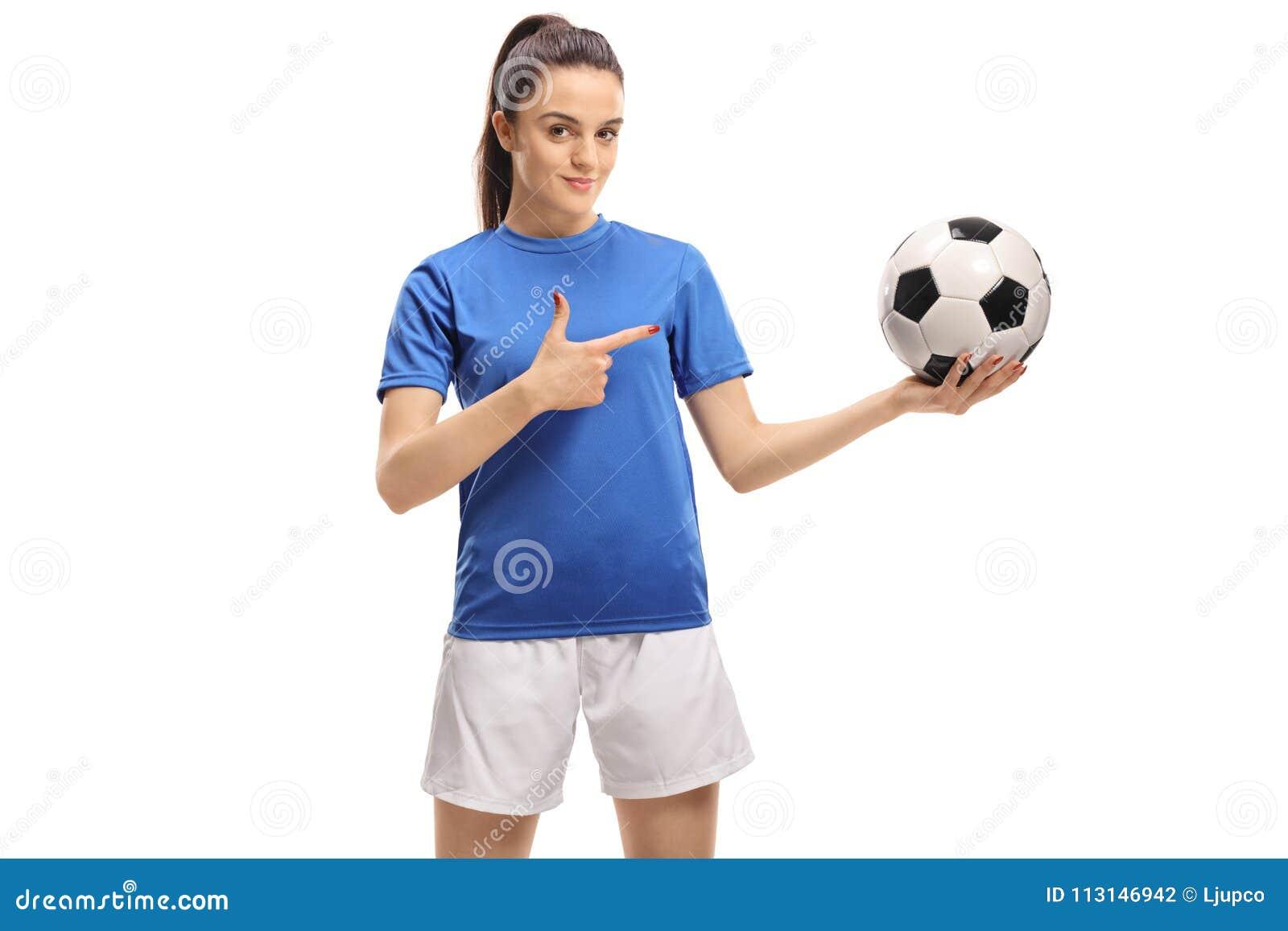 Jogador de futebol fêmea que guarda um futebol e apontar