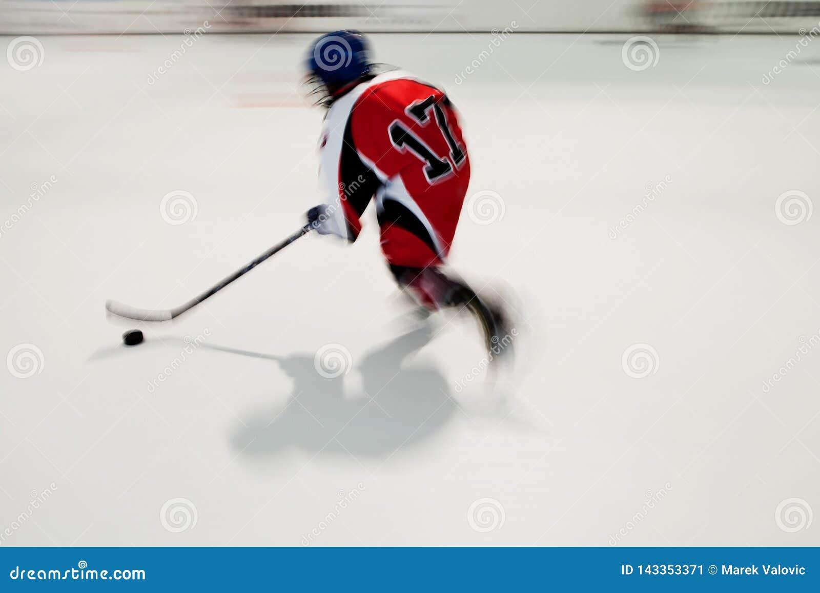 Jogador de hóquei apenas novo no vestido vermelho com número 17 no movimento, movimento obscuro no estádio do gelo