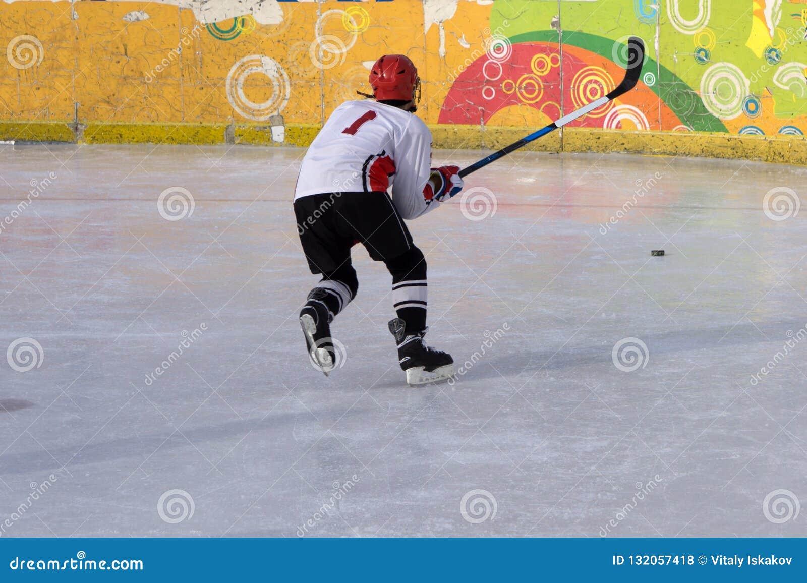 Jogador de hóquei em gelo na ação que retrocede com vara
