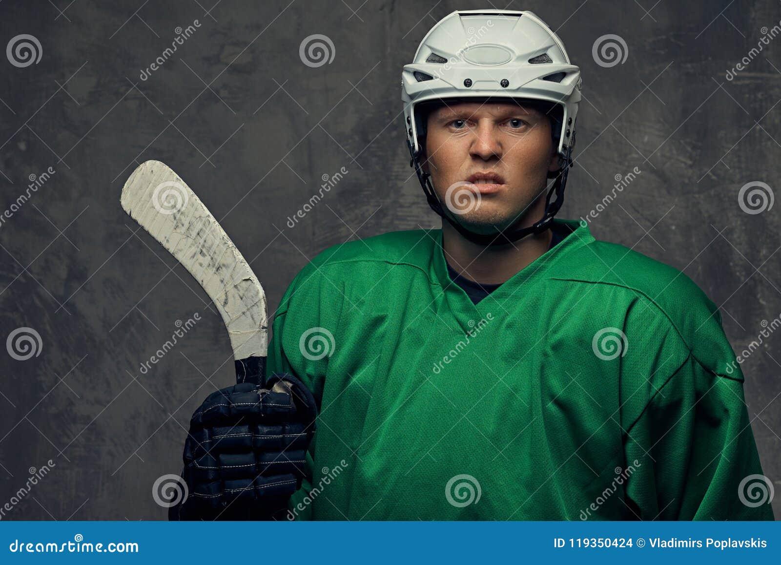 Jogador de hóquei profissional irritado no sportswear verde que está com uma vara de hóquei em um fundo cinzento