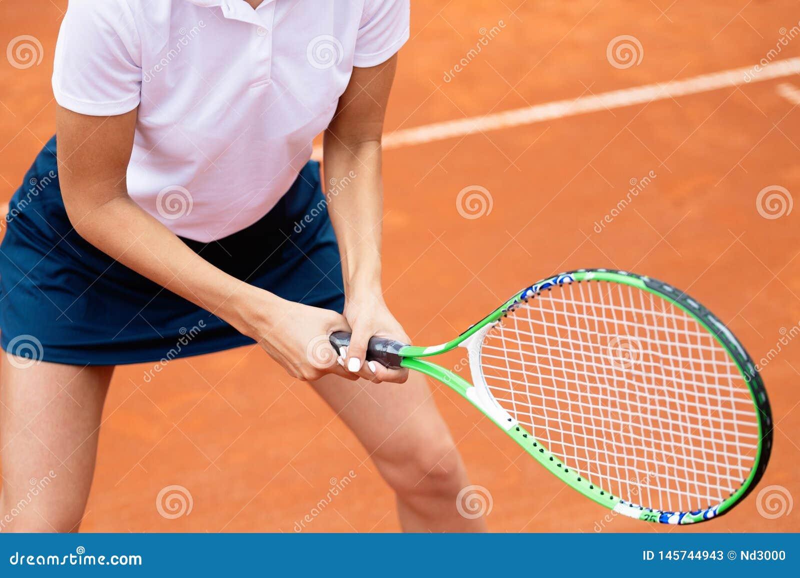 Jogador de t?nis da mulher que sorri ao guardar a raquete durante o f?sforo do t?nis