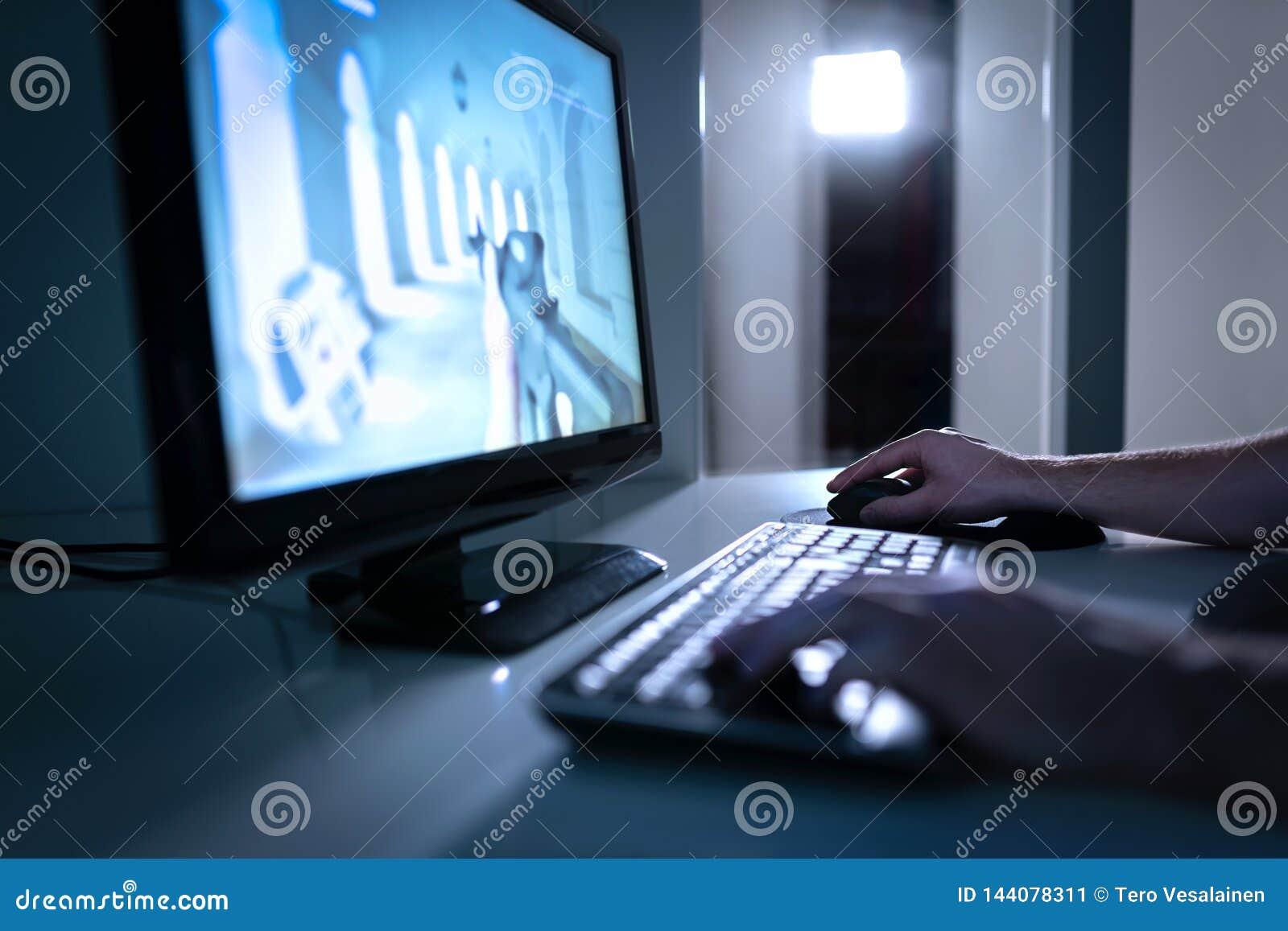 Jogador do jogo de vídeo que joga o videogame dos fps em linha Indivíduo com computador do computador de secretária Conceito de E