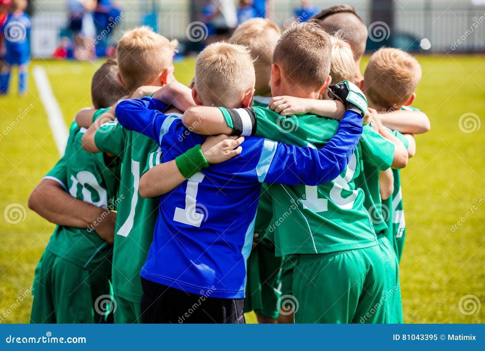 Jogadores de futebol novos do futebol no sportswear O jovem ostenta a equipe de futebol