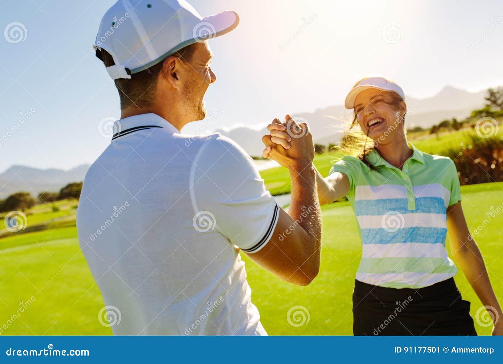 Jogadores de golfe que agitam as mãos no campo de golfe