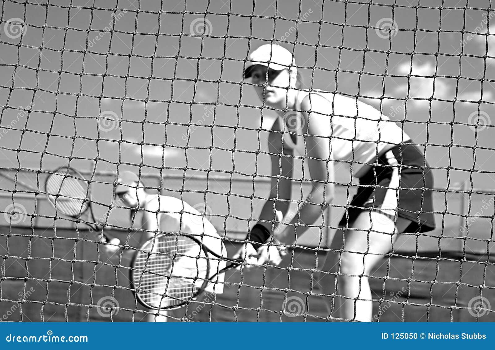 Jogadores de ténis da mulher que olham a câmera através da rede que espera para jogar ao olhar a câmera