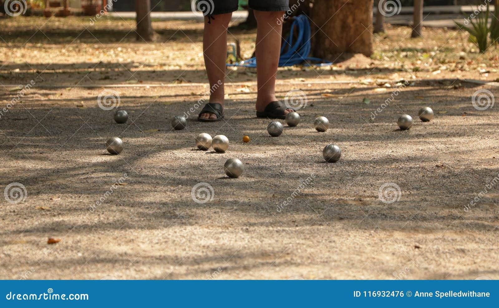 Jogando Petanque no parque - bolas de metal e bola de madeira alaranjada na jarda da rocha com um homem que está no Sun