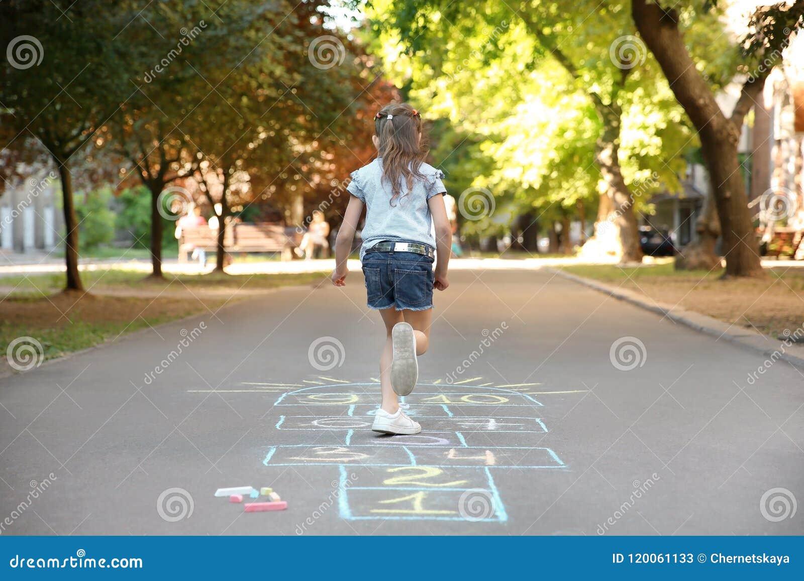 Jogar amarelinha da criança pequena tirado com giz colorido