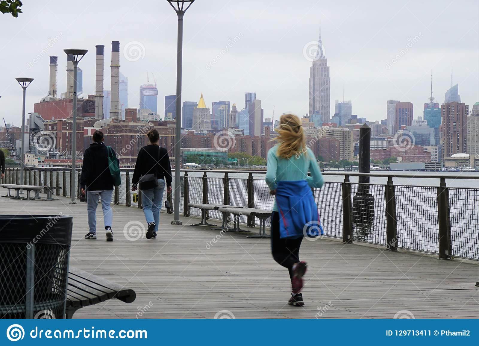 Jogger And Walkers On A Boardwalk In Brooklyn With Nyc Skyline In