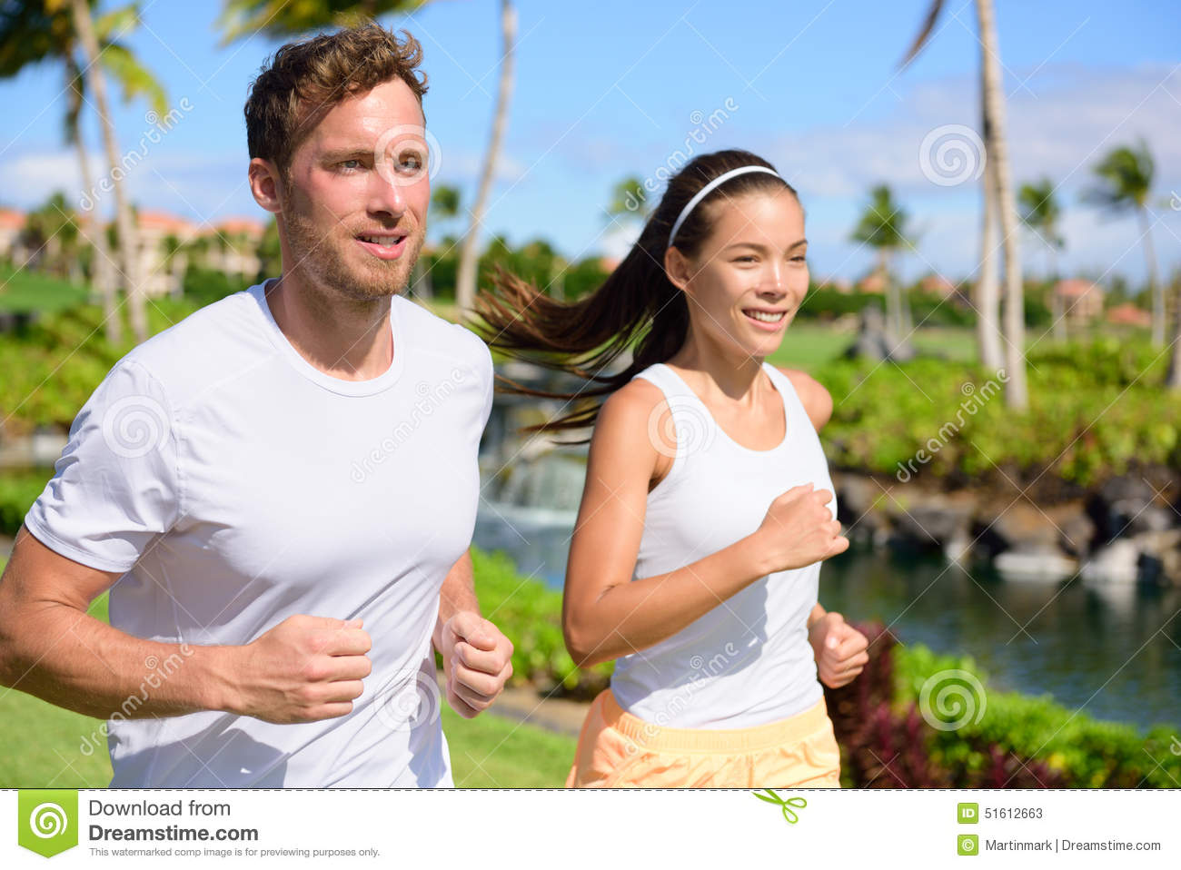 Jogging Couple Of Runners Running Together In Park Stock