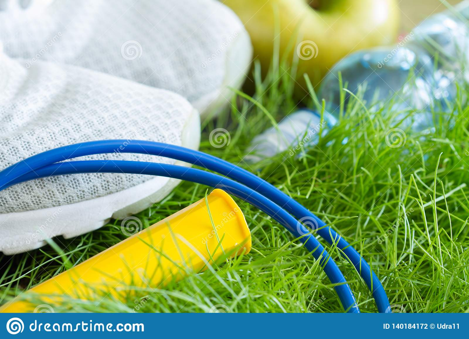Jogging and sport active livestyle concept with sneakers and healthy food outdoor on grass