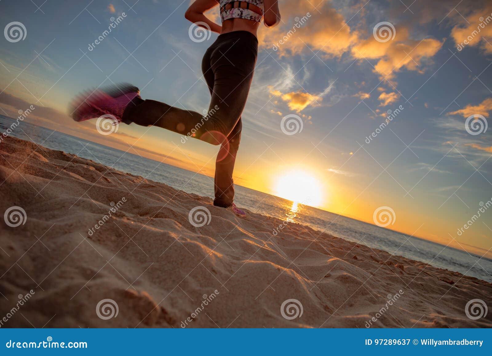 Jogginr apto de la muchacha de la playa de la puesta del sol en la arena contra fondo de la puesta del sol
