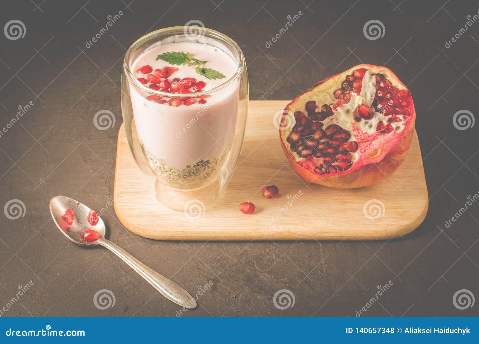 Joghurt Jogurt mit Getreide, Granat und Minze im Glas und in der Granatapfelfrucht auf einem hölzernen Behälter Dunkle backgtound