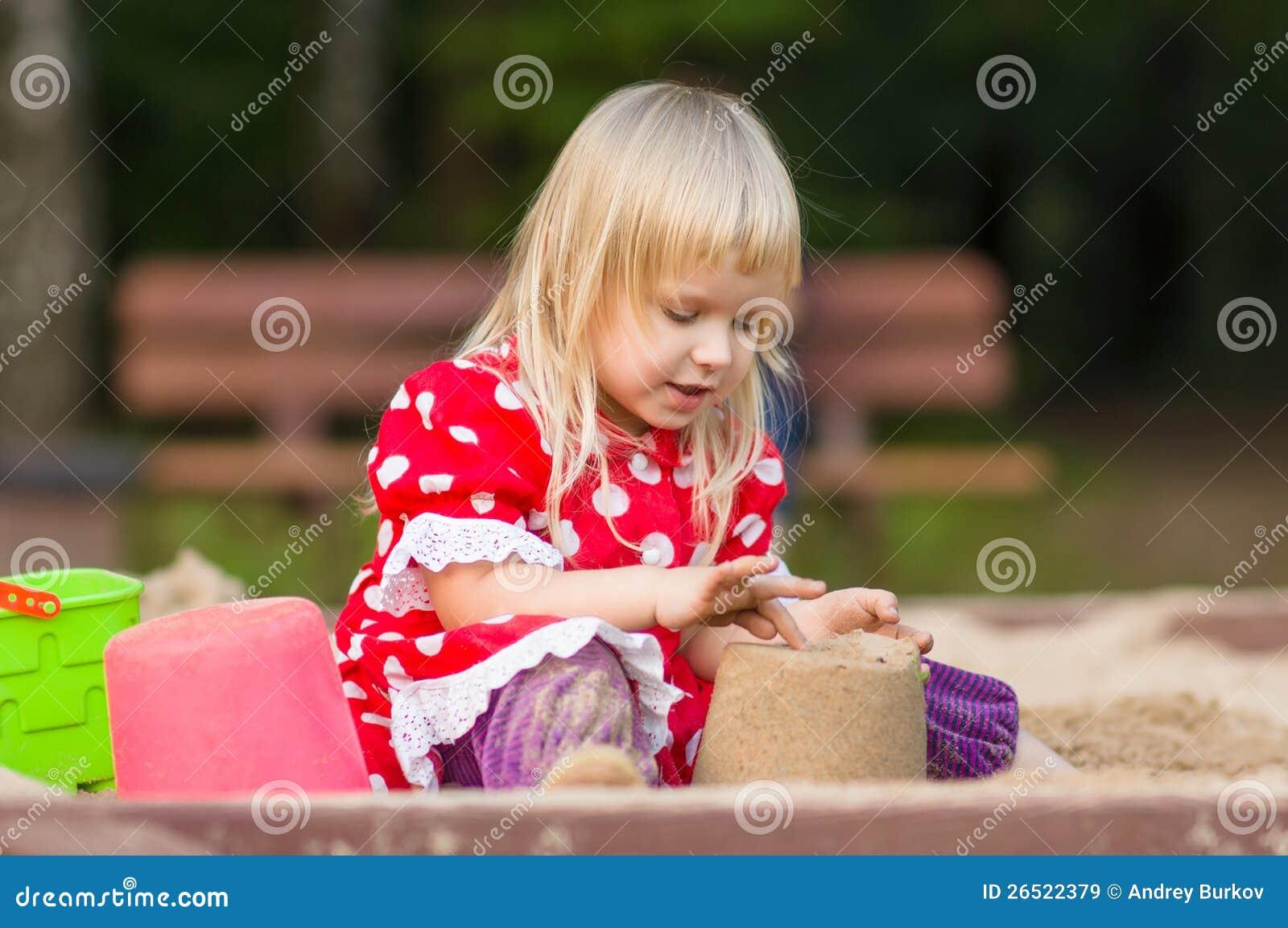 Jogo adorável da menina com os brinquedos na caixa de areia