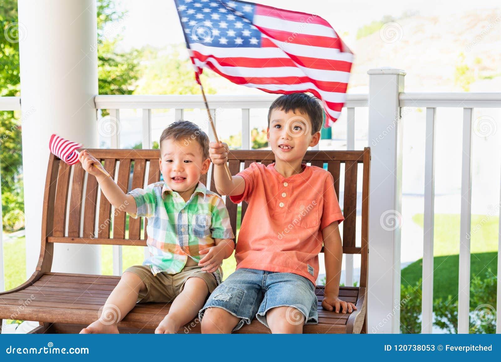 Jogo caucasiano chinês bonito dos irmãos da raça misturada com bandeiras americanas