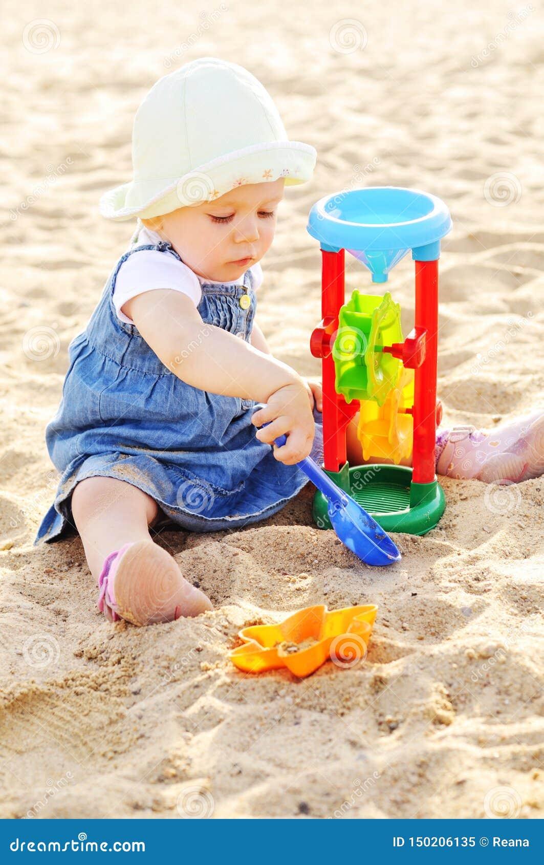 Jogo da menina da criança brinquedos na areia