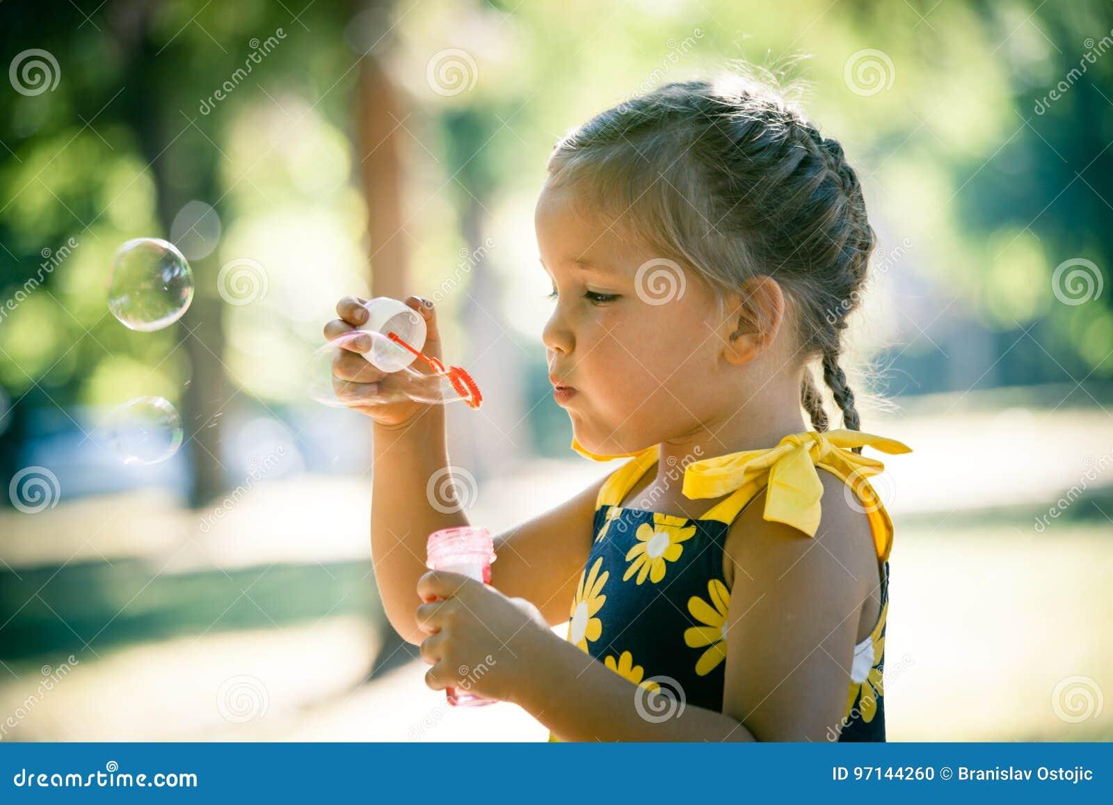 Jogo da menina no fim do perfil das bolhas de sabão do sopro do parque acima