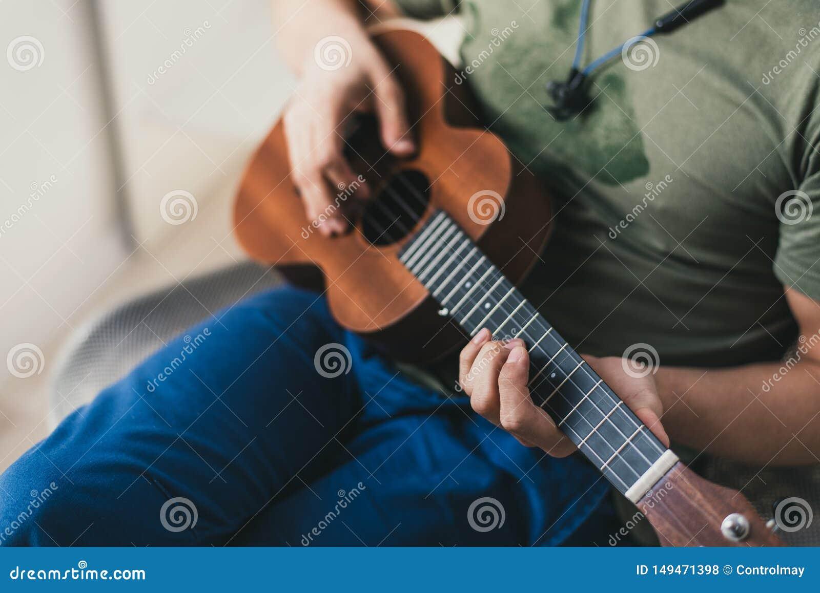 Jogo da uquelele um homem que joga uma guitarra pequena o executor escreve a música na uquelele em casa