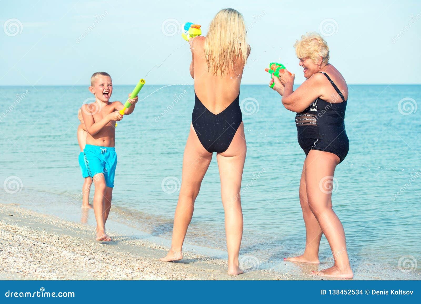 Jogo de crianças com minhas mãe e avó com as pistolas de água na praia Adultos novos