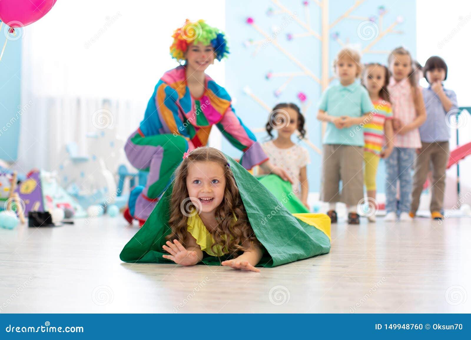 Jogo de crianças com o palhaço na festa de anos no centro de entretenimento