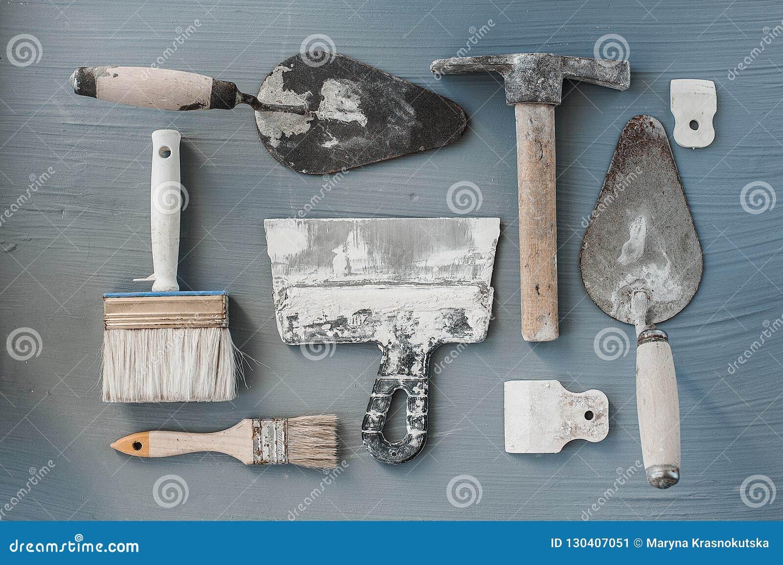 Jogo de facas de massa de vidraceiro Espátulas com o almofariz restante Gastarbeiter ou conceito do trabalhador imigrante