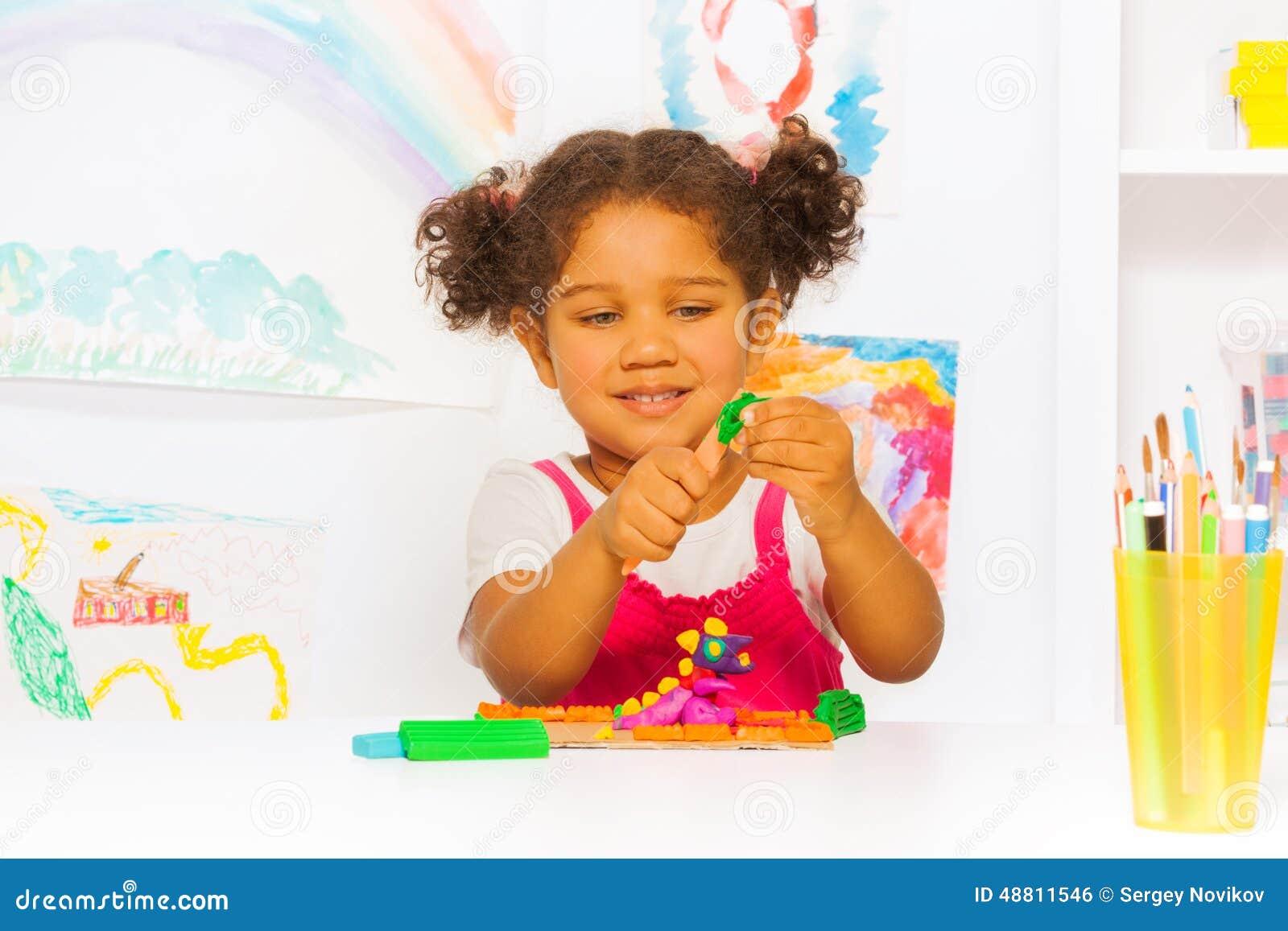 Jogo de vista latino-americano pequeno da menina com plasticine