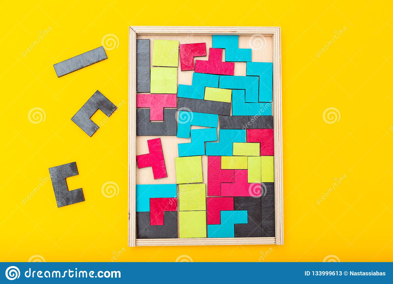 Jogo do Tangram de madeira e colorido no fundo amarelo Configuração lisa