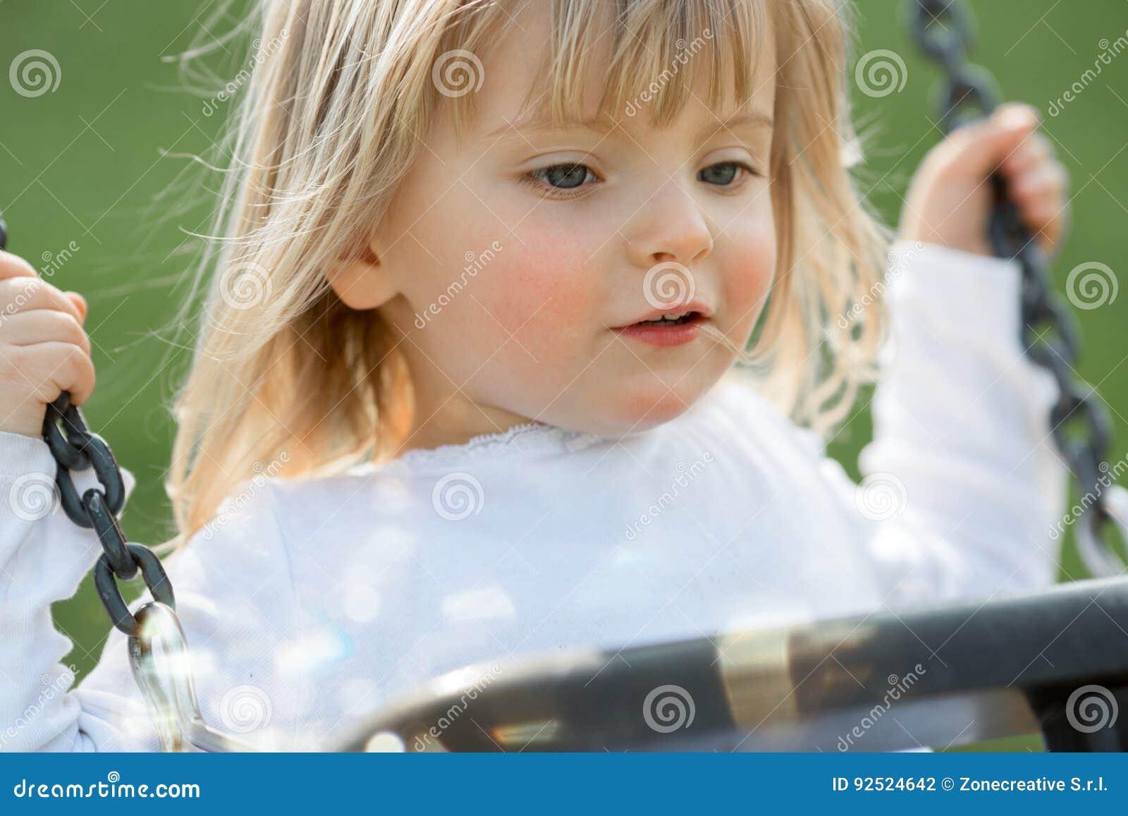 Jogo exterior de sorriso feliz do fim real louro caucasiano novo da menina dos povos do bebê no balanço