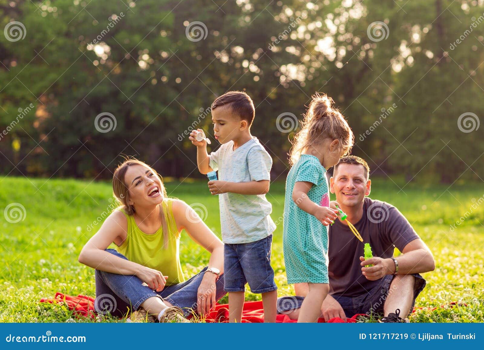 Jogo masculino e fêmea feliz com crianças fora