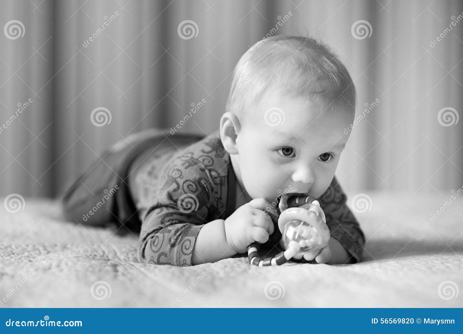 Jogo velho de seis meses do bebê com brinquedos