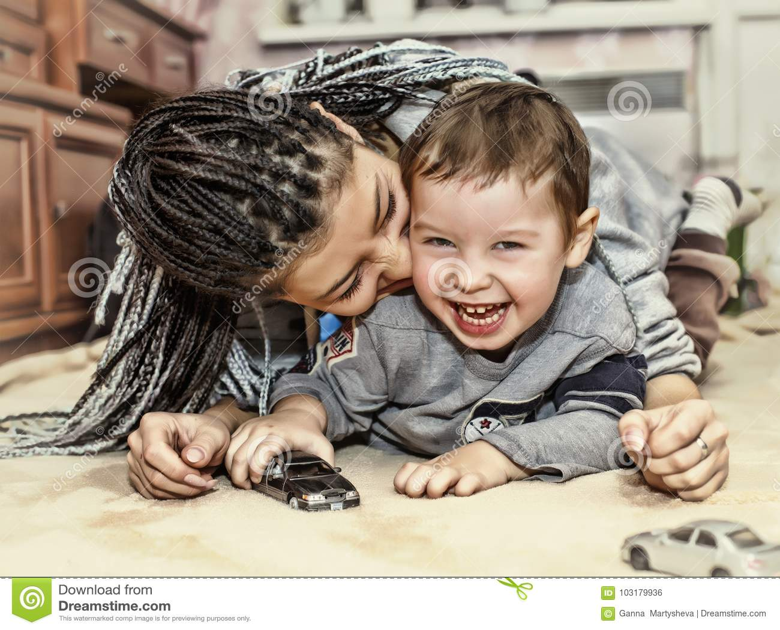 Jogos de pele escura da mãe com seu filho A mamã latino-americano joga e ri com seu filho pequeno Conceito: Dia feliz do ` s da m