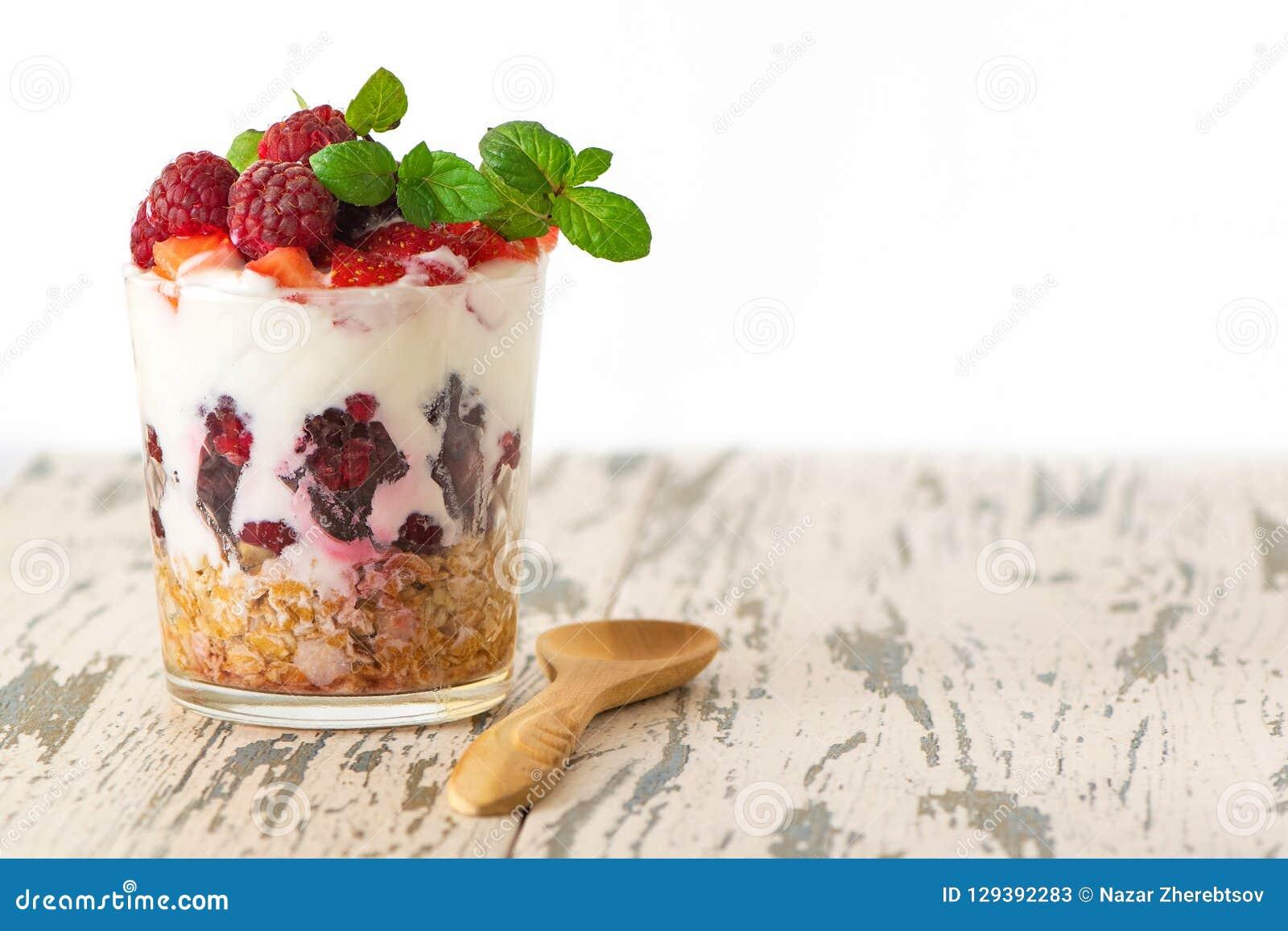 Jogurt z muesli i jagody w szkle na lekkim drewnianym stole