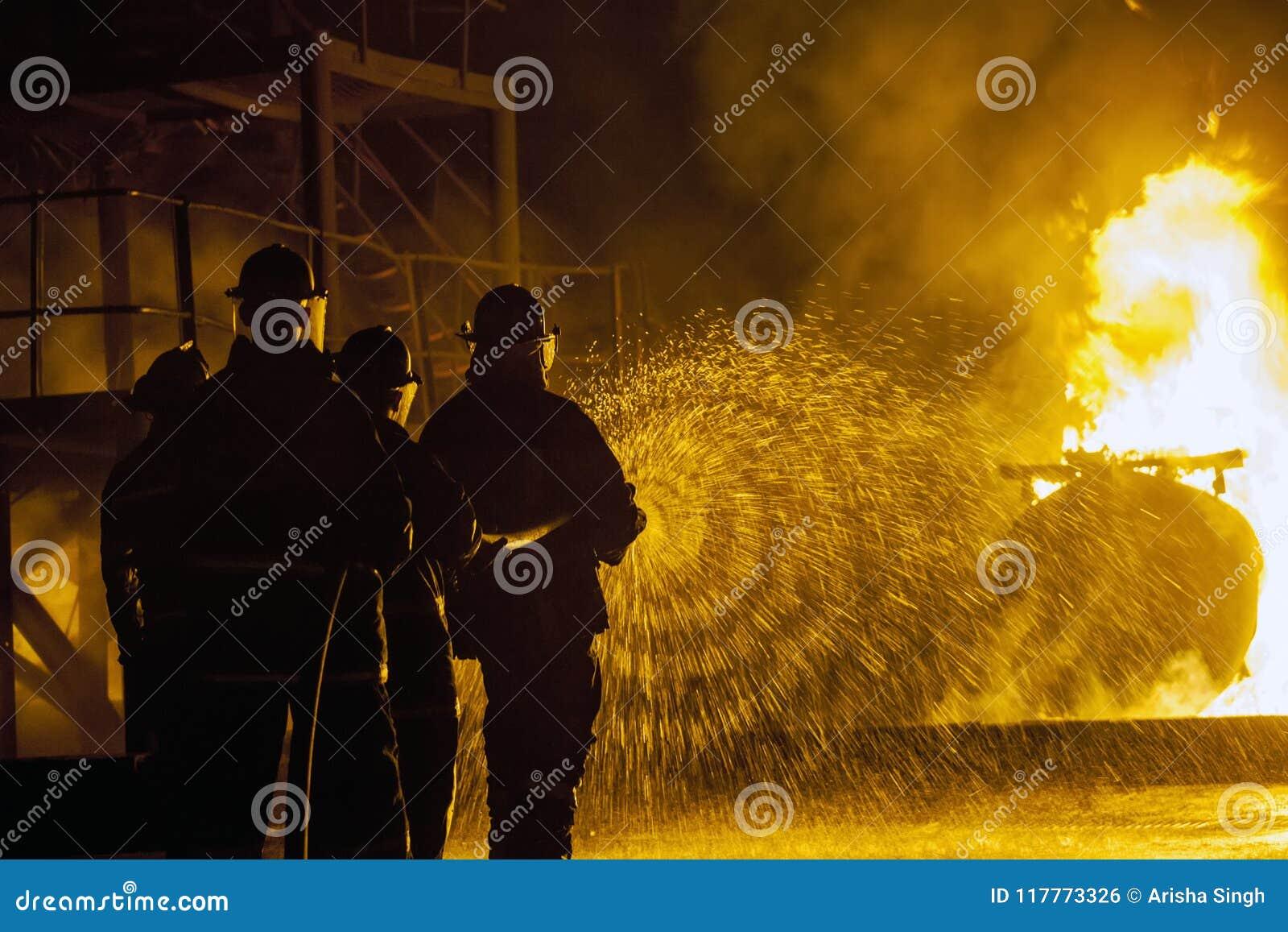 JOHANNESBURG, AFRIQUE DU SUD - mai 2018 sapeurs-pompiers pulvérisant l eau au réservoir brûlant pendant un exercice d entraînemen